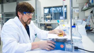 Ein Wissenschaftler arbeitet an einem Versuchsaufbau im Labor.